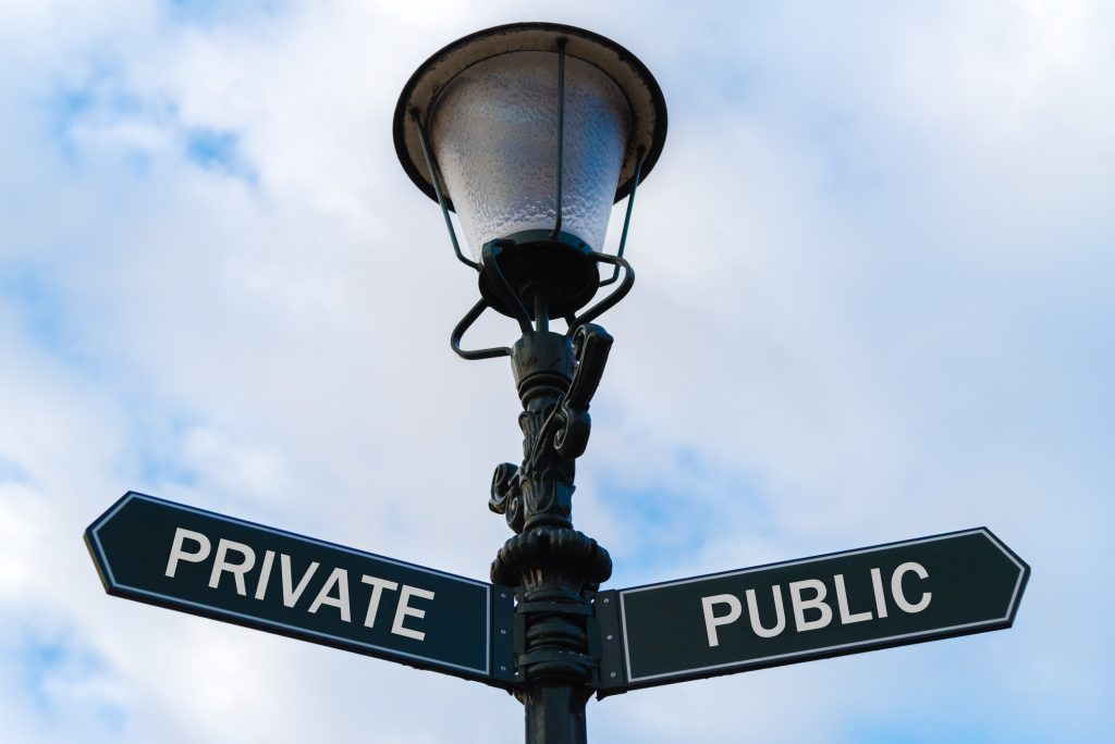 Street lighting pole with two opposite directional arrows over blue cloudy background. Private versus Public concept.